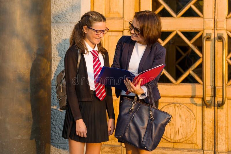 Le haut maître d'école parle à l'étudiante près de l'entrée principale de l'école photos stock