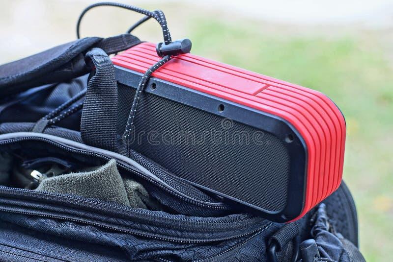 Le haut-parleur portatif rouge noir se trouve sur un sac ouvert photo libre de droits