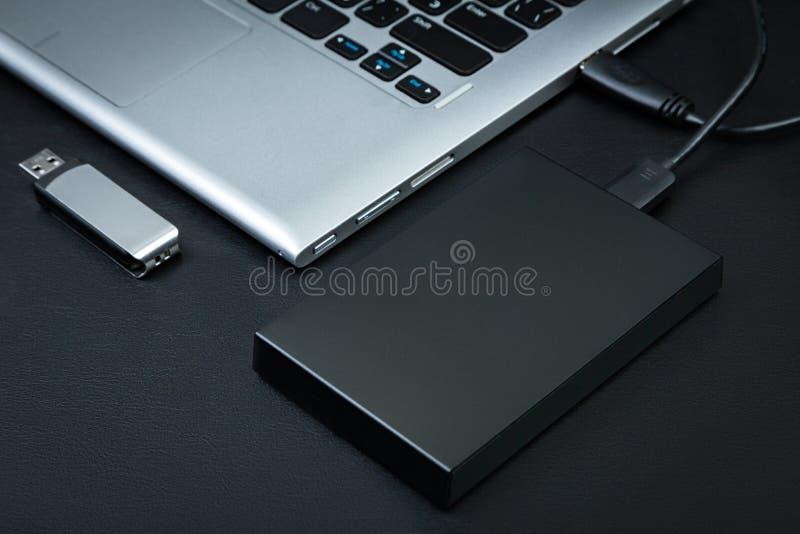 Le hdd externe s'est relié à la commande d'ordinateur portable et d'instantané d'USB sur un fond noir photos stock
