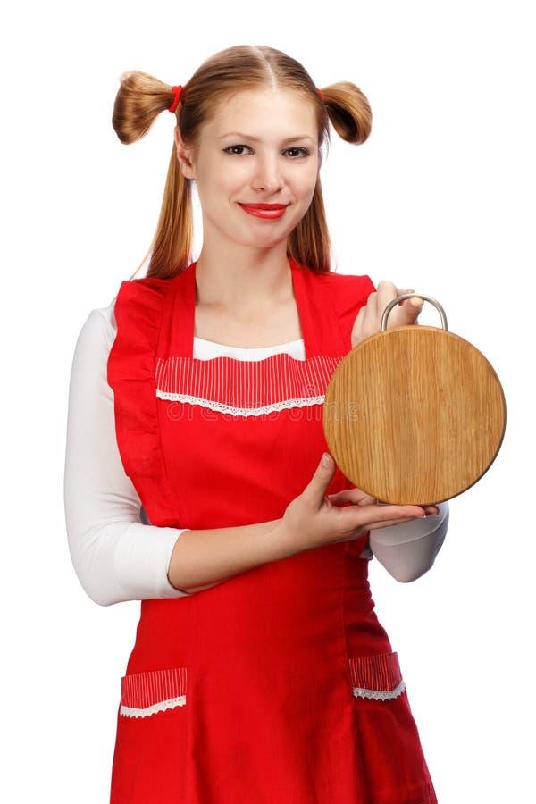 Le hemmafrun i rött förkläde med roliga hästsvansar och träc arkivbilder
