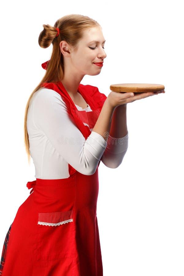 Le hemmafrun i rött förkläde med roliga hästsvansar och träc arkivfoto