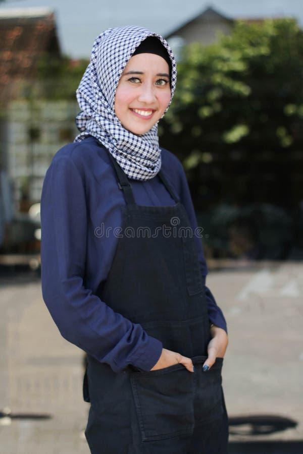 Le Hijab den arabiska kvinnan med förklädet som framme poserar av exponeringsglasdörr som välkomnar en dräkt royaltyfri bild