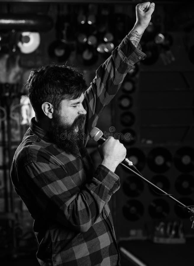 Le hippie aime chanter sur l'étape L'homme avec le visage enthousiaste tient le microphone, chanson de chant, photographie stock libre de droits