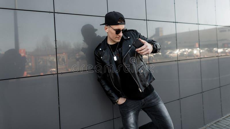 Le hippie américain de jeune homme dans une veste en cuir noire dans une casquette de baseball dans des jeans dans un T-shirt se  photo stock
