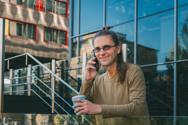 Le hippie attirant de jeune homme parle sur le téléphone et le café potable de rue d'une tasse de carton près des affaires en ver images libres de droits