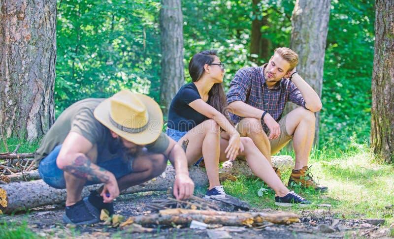 Le hippie barbu brutal campant d'homme de forêt d'amis de société prépare le feu dans la forêt comment feu de construction dehors image stock