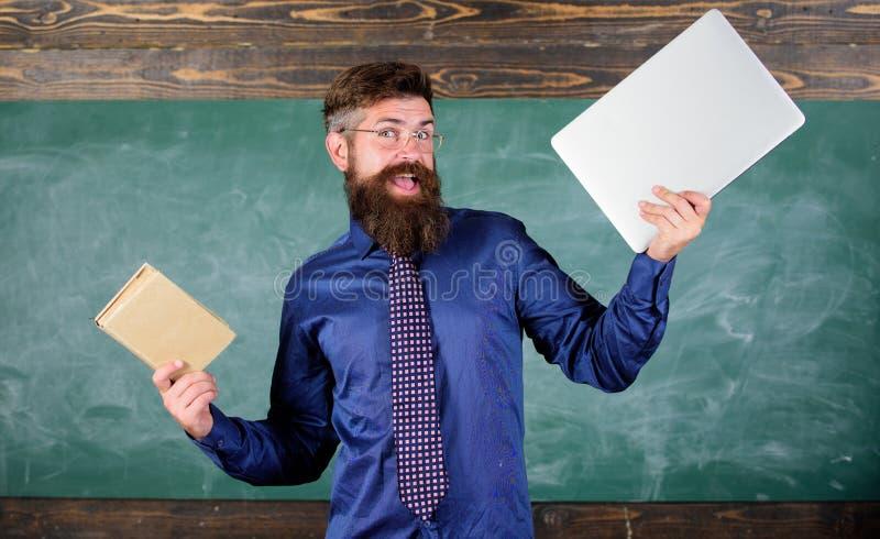 Le hippie barbu de professeur tient le livre et l'ordinateur portable Ce qui vous préférerait Professeur choisissant l'approche m images libres de droits