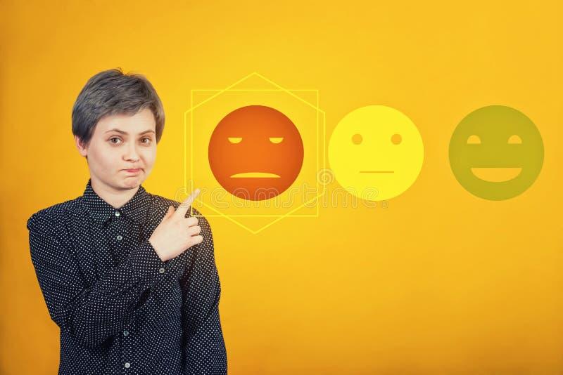 Le hippie douteux de femme dirigeant l'index de côté, expression incertaine de visage, choisissent l'estimation de retour négatif photographie stock libre de droits