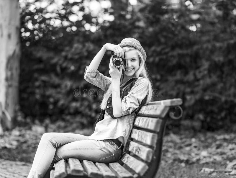 Le hippie prenant la photo avec le rétro appareil-photo de photo se reposant sur soit image stock