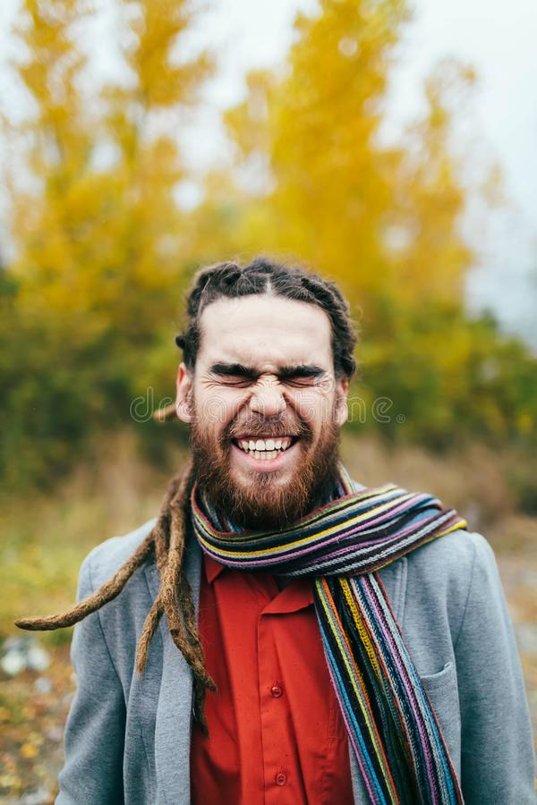 Le hippie sourit Un homme élégant avec des dreadlocks et barbe dans une chemise rouge et une veste grise Marié posant sur la natu images stock