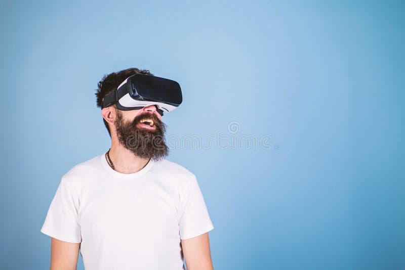 Le hippie sur le visage de sourire apprécient la réalité virtuelle avec l'instrument Homme avec la barbe en verres de VR, fond bl image libre de droits