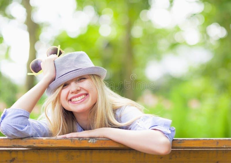 Le hipsterflickasammanträde på bänk i parkera arkivbild
