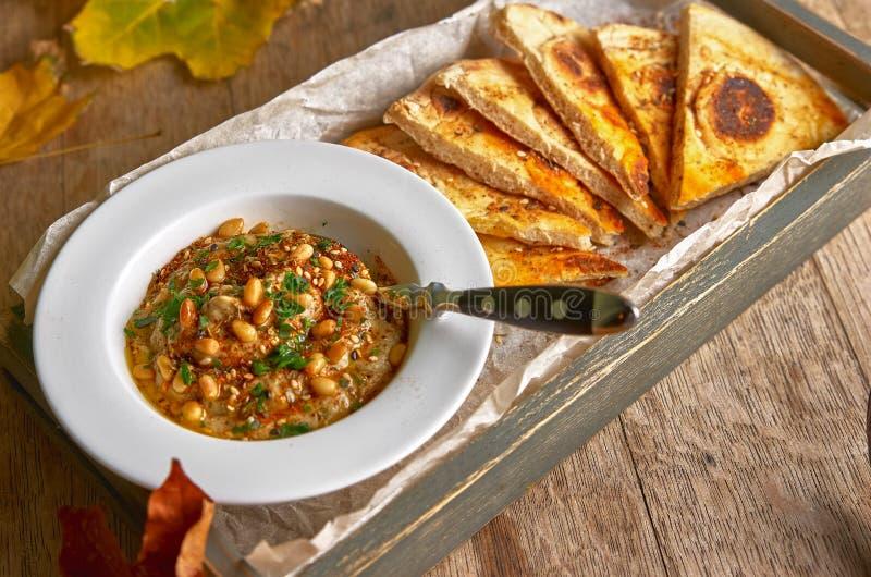 Le houmous traditionnel d'apéritif de Moyen-Orient a servi avec du pain pita frais et des herbes, assaisonnés avec l'huile et le  image libre de droits