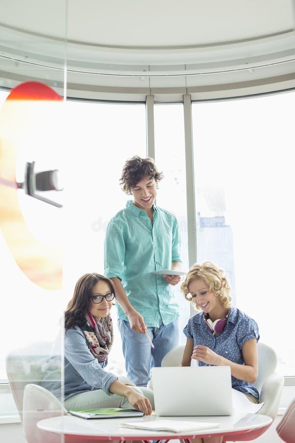 Le idérika businesspeople som i regeringsställning diskuterar över bärbara datorn arkivfoto