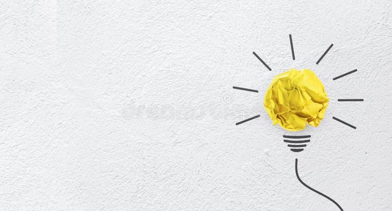 Le idee con carta gialla hanno sgualcito la palla sul fondo della parete fotografia stock