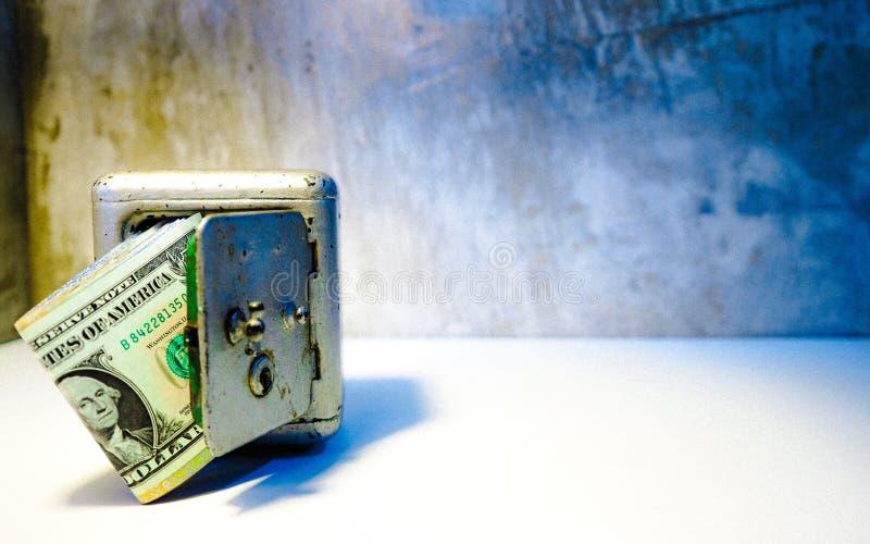 Le idee di risparmio tengono il biglietto del dollaro in cassaforti ed in BAC fotografie stock libere da diritti