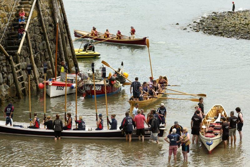 Le imbarcazioni a remi ed i gruppi atterrano all'entrata di porto a Clovelly, Devon fotografie stock