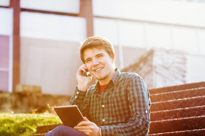 Le innehavet för den unga mannen boka och tala på mobiltelefonen i a royaltyfria foton