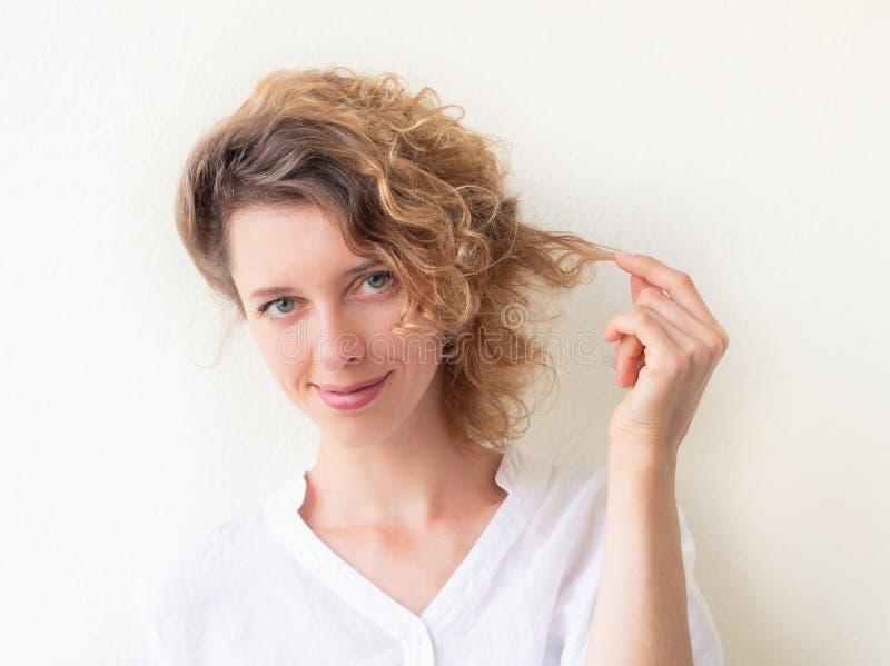 Le innehavtråden för ung kvinna av hennes lockiga hår arkivbild