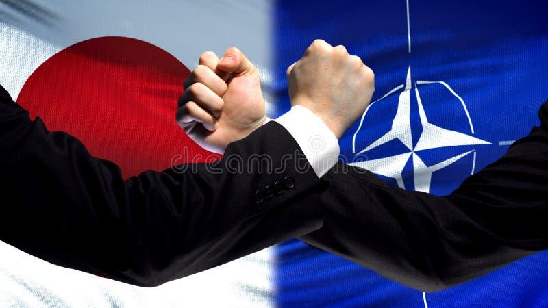 Le Japon contre la confrontation de l'OTAN, désaccord de pays, poings sur le fond de drapeau photographie stock libre de droits