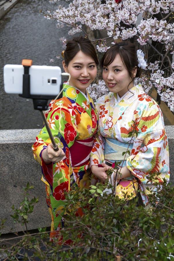 Le Japon, Kyoto, 04/05/2017 Les jeunes filles japonaises dans le kimono prennent un selfie sur le fond de Sakura photo stock