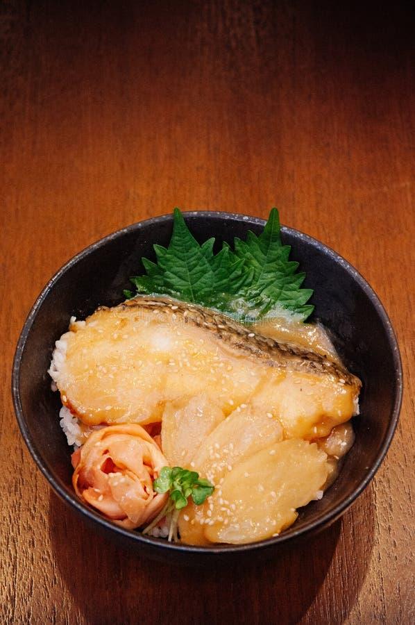 Le Japonais a grillé le bol de riz de donburi de poissons de neige sur la table en bois en Re images stock