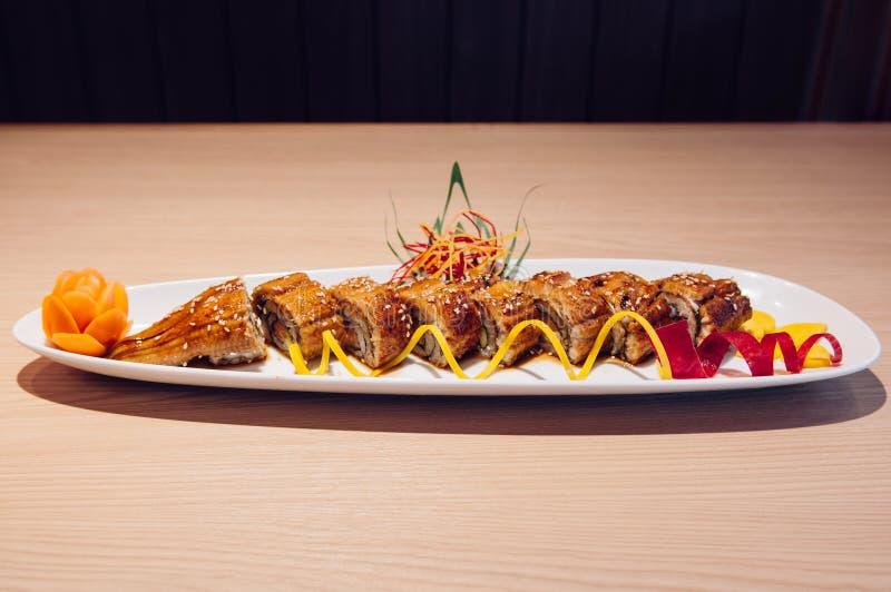 Le Japonais a grillé le petit pain d'Unagi Maki sur le fond blanc d'obscurité de plat photographie stock libre de droits