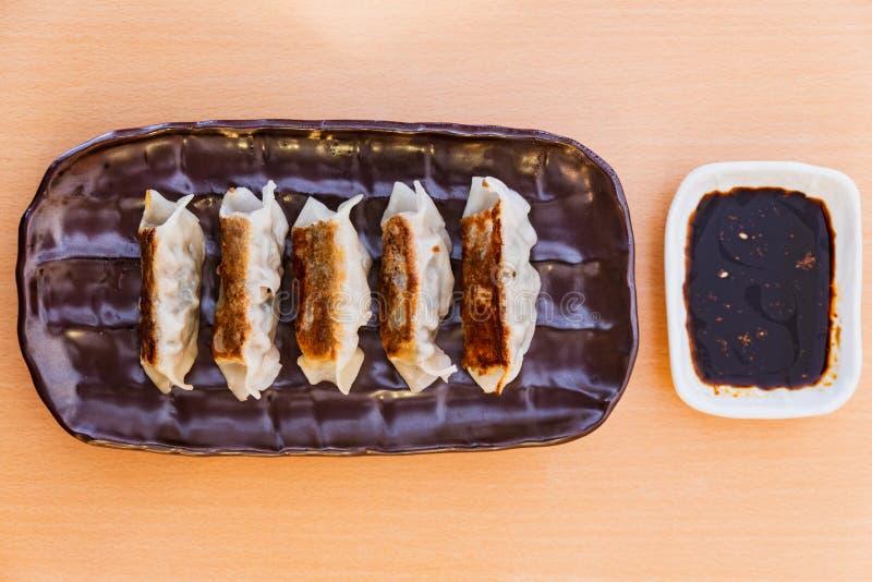 Le Japonais Pan-Fried Dumplings de Gyoza a servi avec de l'huile de sauce et de sésame photos libres de droits