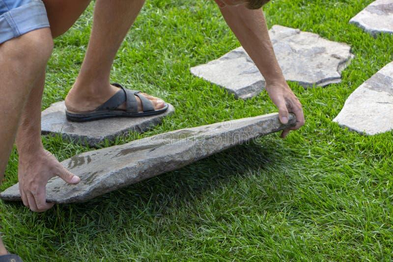 Le jardinier monte un chemin étape-par-étape de pierre naturelle à la pelouse images stock