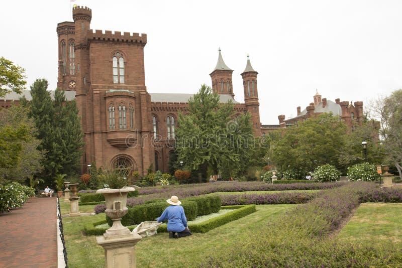 Le jardinier travaille devant un château photo libre de droits