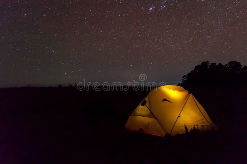 Le jaune éclairent la tente sous le ciel étoilé de nuit photographie stock