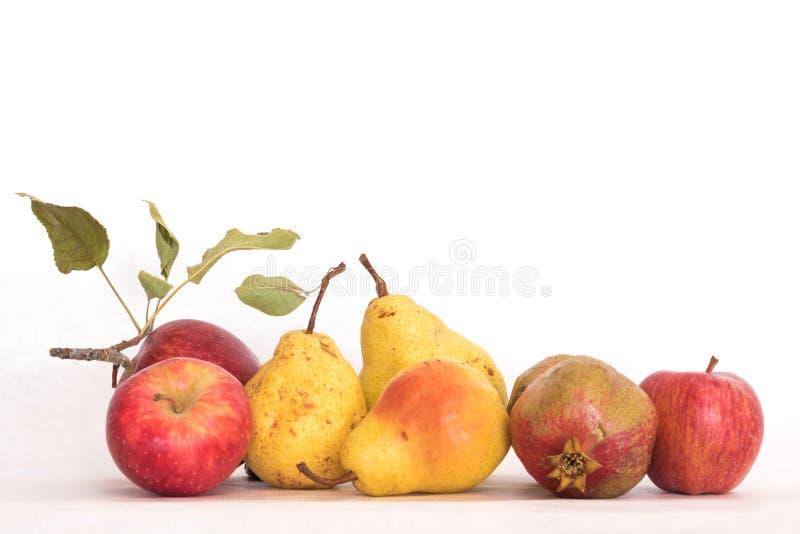 Le jaune trois mûr a pelé les pommes rouges de poires, une grenade, le beau tir organique frais de studio de tiges et les feuille photos libres de droits
