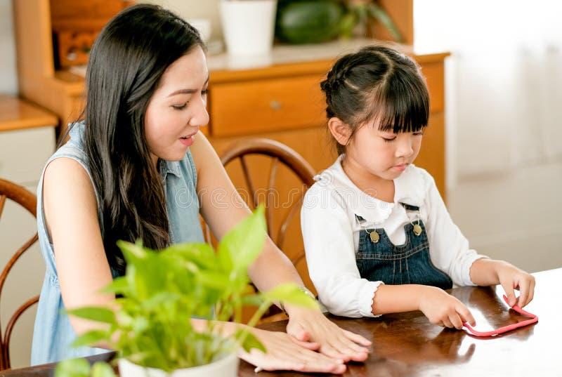 Le jeu asiatique de mère et de fille ainsi que l'argile dans la cuisine et eux semblent heureux images stock