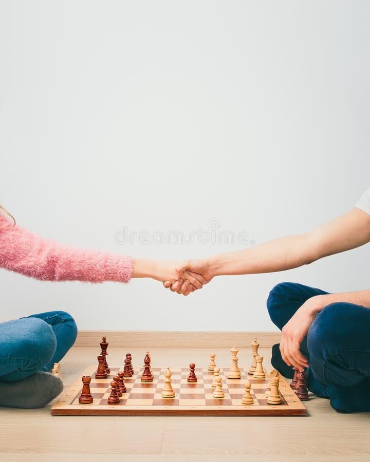 Le jeu d'échecs est terminé Poignée de main de fille et de garçon après le jeu d'échecs de finition, remerciant du jeu images libres de droits