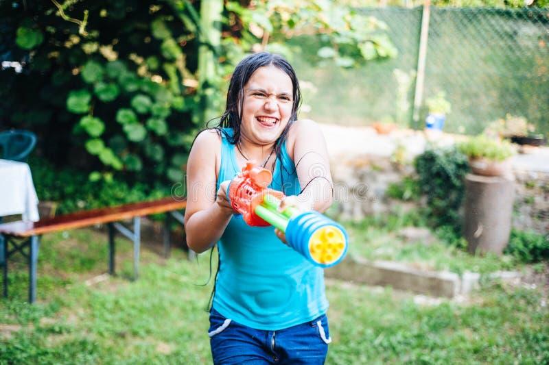 le jeu d'enfants dans le jardin avec de l'eau les armes à feu et fusille sur un sunn photographie stock libre de droits