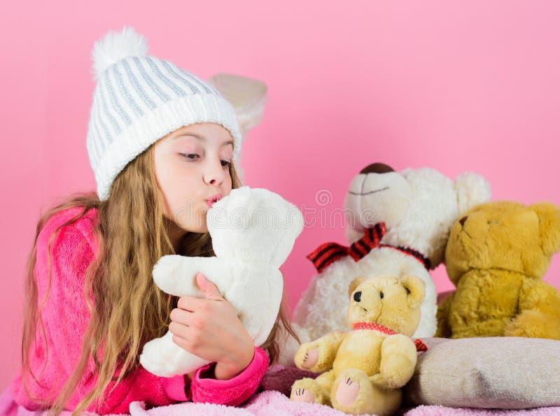 Le jeu de petite fille d'enfant avec le nounours mou de jouet concernent le fond rose Les ours de nounours aident des enfants à m photo libre de droits