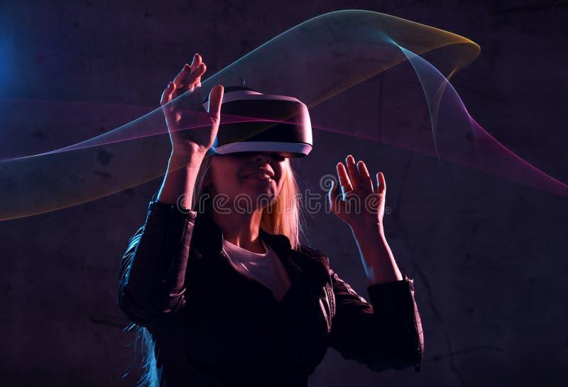 Le jeu de réalité virtuelle de jeu de jeune fille portent des lunettes de vr et explorent la réalité alternative femme dans l'esp image libre de droits