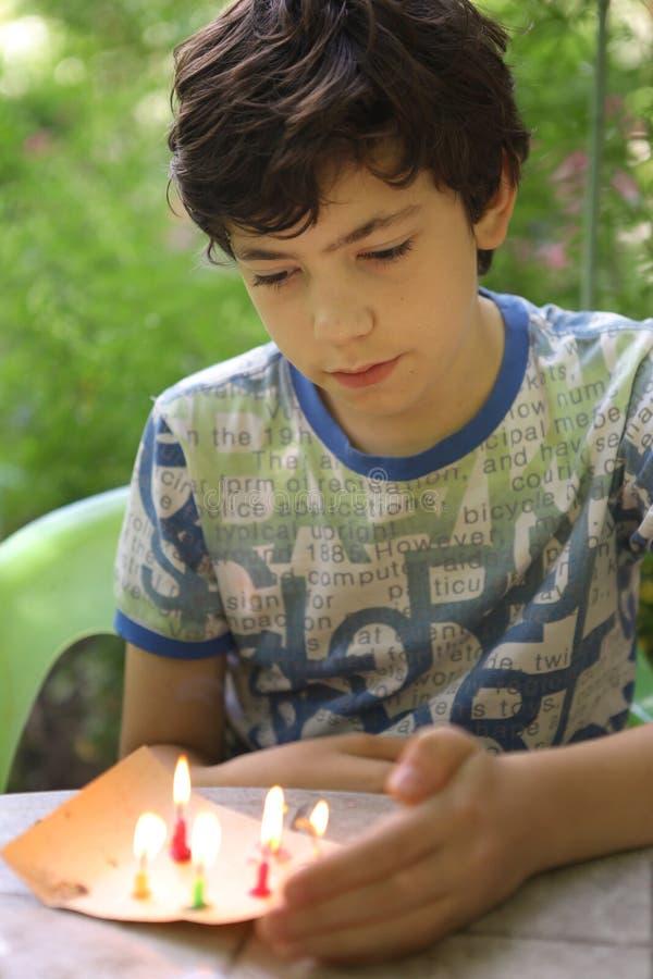 Le jeu malfaisant de garçon d'adolescent avec des bougies brûlent le feu images stock