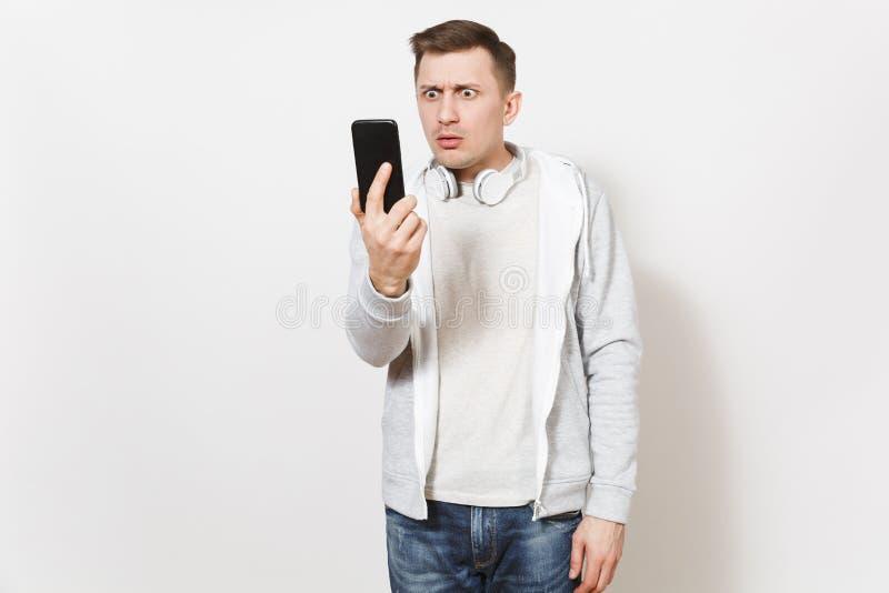 Le jeune étudiant bel triste d'homme dans le T-shirt et le pull molletonné léger avec des écouteurs autour de cou prend son visag image libre de droits