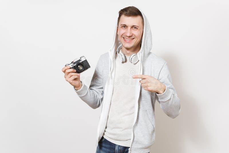 Le jeune étudiant de sourire bel d'homme dans le T-shirt et le pull molletonné léger avec le capot avec des écouteurs tient la ré image libre de droits