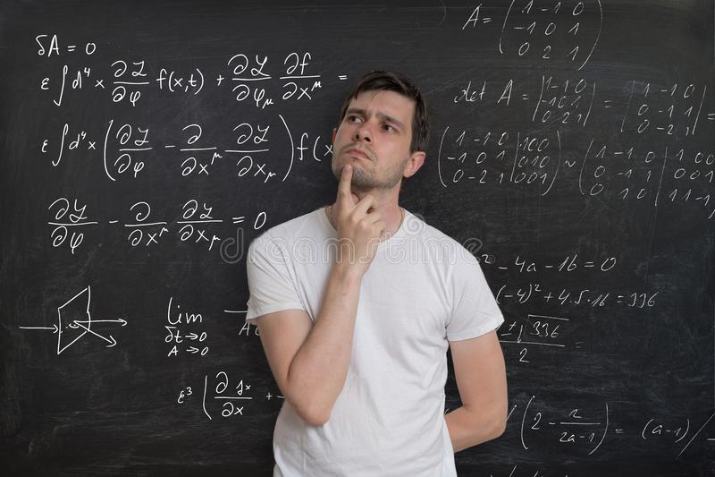 Le jeune étudiant est pensant et résolvant le problème mathématique Formule de maths sur le tableau noir à l'arrière-plan photo stock