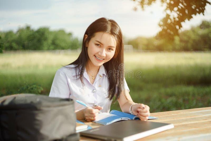 Le jeune étudiant féminin écrit une note et une tâche avec un ordinateur portable à coté en dehors du campus avec le backgrou ver image libre de droits