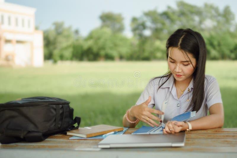 Le jeune étudiant féminin écrit une note et une tâche avec un ordinateur portable à coté en dehors du campus avec le backgrou ver image stock
