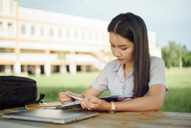 Le jeune étudiant féminin écrit une note et une tâche avec un ordinateur portable à coté en dehors du campus avec le backgrou ver photos libres de droits