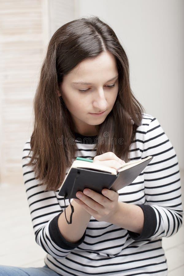 Le jeune étudiant focalisé prend des notes dans le carnet utilisant le crayon, sitt photos stock