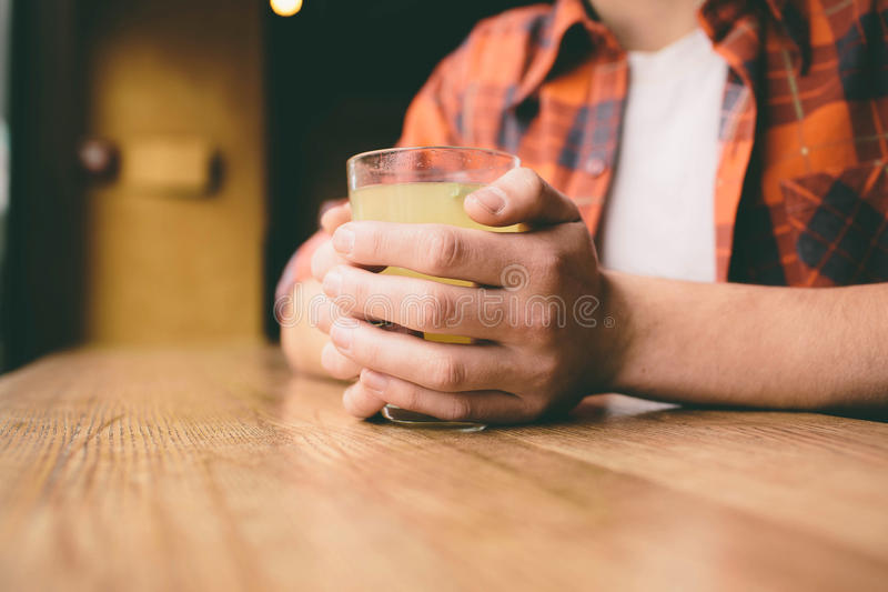 Le jeune étudiant s'assied dans le restaurant et goûte une boisson chaude thé potable d'homme au café photo libre de droits