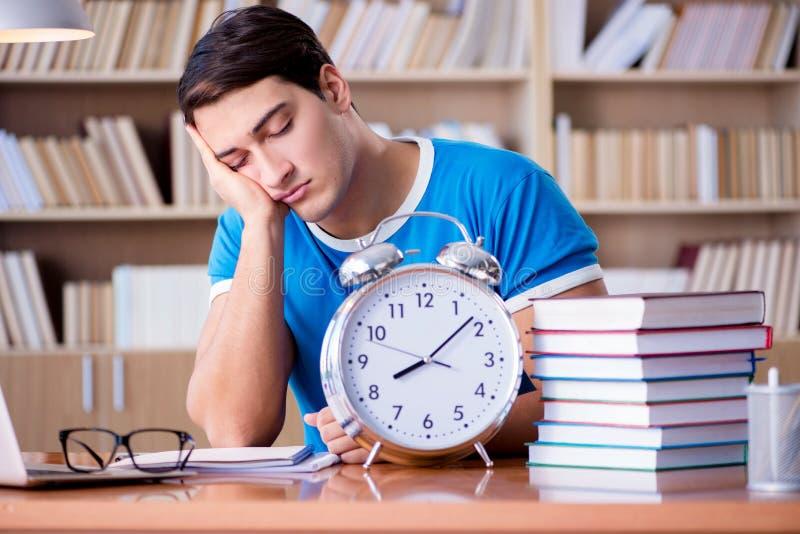 Le jeune étudiant se préparant tard à ses examens photo stock