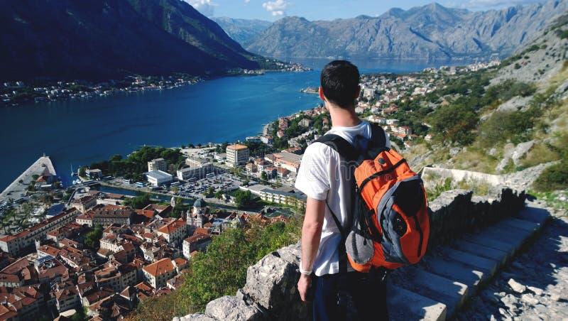 Le jeune adolescent admire la vue pendant la montée à la forteresse dans Kotor dans Monténégro Brune masculine dans le T-shirt bl photo libre de droits