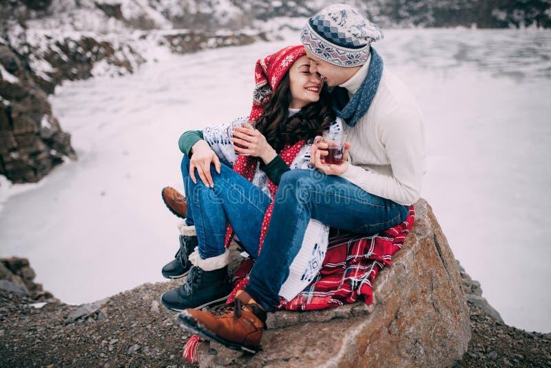 Le jeune ajouter aux tasses de thé chaud dans leurs mains se repose à la roche et sourit pendant la promenade d'hiver photos stock
