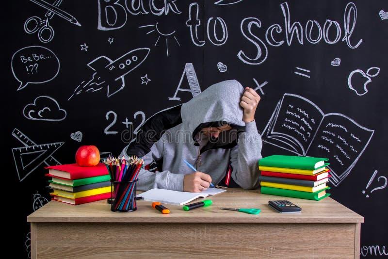 Le jeune apathique et indifférent s'asseyant au bureau avec une tête s'est penché sur les poings, entourés avec l'école image stock